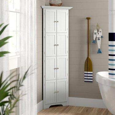 White 8-door corner bathroom cabinet in coastal-themed bathroom with tub and hardwood floors