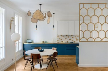 art deco kitchen with oval tulip dining table and blue cabinets