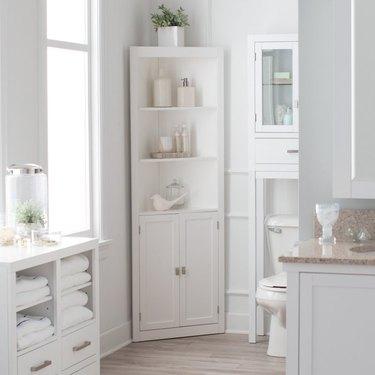 White corner bathroom cabinet and hardwood floors