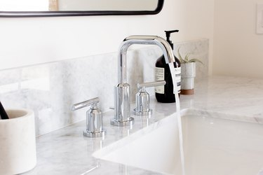 white marble sink with silver fixtures featuring water running and Aesop hand soap
