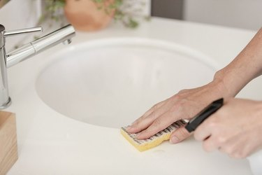 Cleaning bathroom sink with spray and sponge