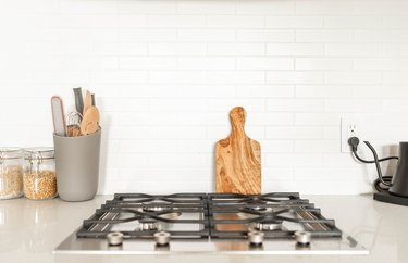 cooktop on white countertop and white tile backsplash