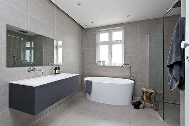 minimalist bathroom vanity with large white bathtub.