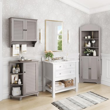 Taupe corner bathroom cabinet and white sink in wallpapered bathroom with hardwood floors