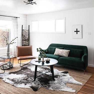 living room rug idea with a green couch in a living room with a small round coffee table, and a brown and white cowhide rug layered over a jute rug