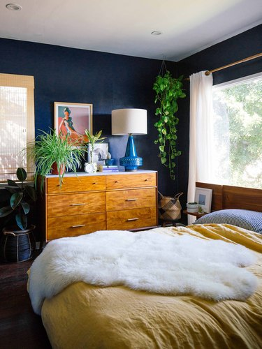 blue bohemian bedroom idea with wood dresser and yellow bedspread