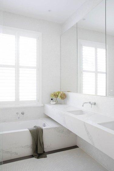 minimalist bathroom vanity with marble counter and tub