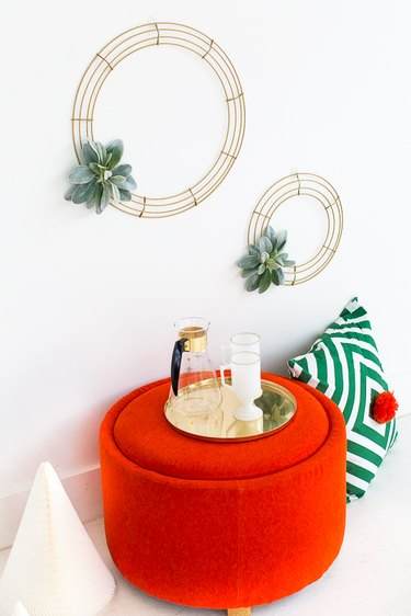 Simple DIY minimalist wreath above red ottoman and green patterned pillow