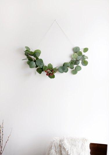 DIY minimalist wreath with greenery on white wall