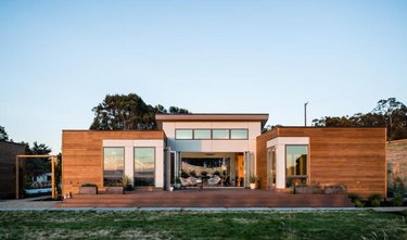 Modern prefab home in warm woods with a flat roof