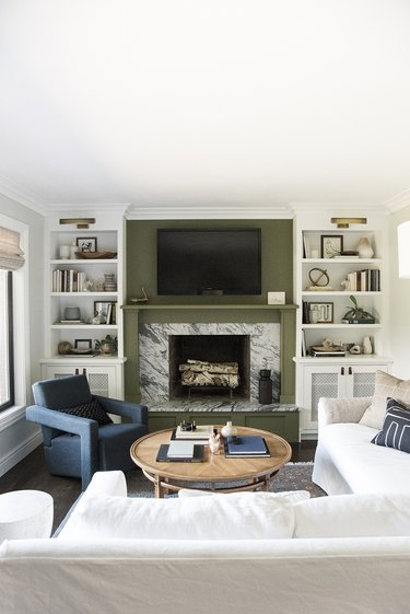 rustic family room ideas with green accent wall and marble fireplace