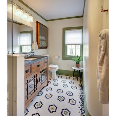 arts and crafts bathroom with patterned hex floor tile and green painted trim