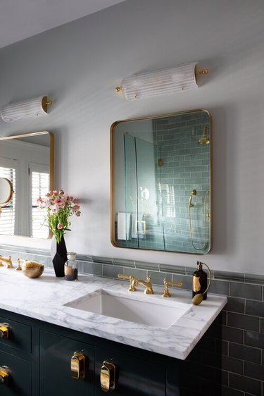 arts and crafts bathroom with brass hardware and marble countertop
