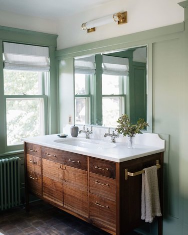 wood vanity in arts and crafts bathroom with green painted wainscoting
