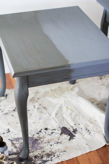 Half of end table coated in dark wax