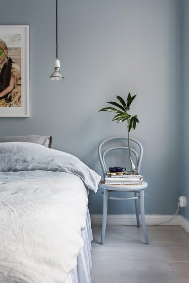 monochrome blue bohemian bedroom idea with artwork hanging above bed