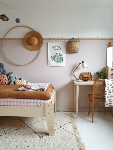 pink and brown minimalist girl bedroom with hula hoop and peg rail