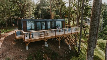 Shipping container modern prefab home on a hillside with trees