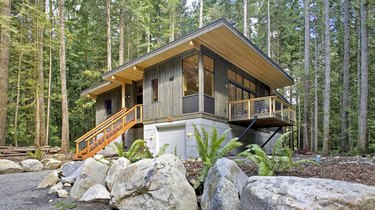 Cabin-inspired modern prefab home with flat roof in pine trees