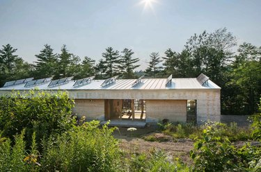 Modern prefab home with solar panels surrounded by trees