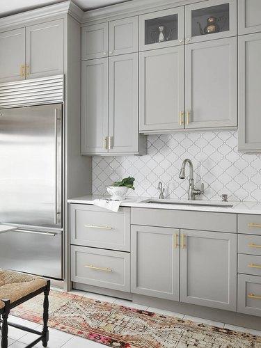 gray kitchen with white arabesque tile backsplash