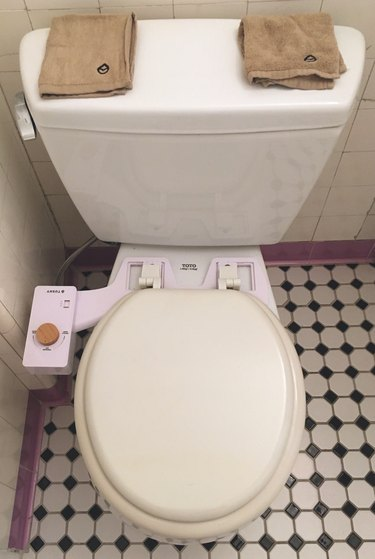 Tushy Classic bidet on Toto toilet in bathroom with black and white floor tile