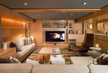 pine basement family room ideas with built-in entertainment system, cream couches, and recessed lighting