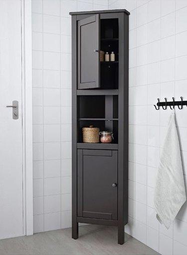 Tall brown corner bathroom cabinet in white-tiled bathroom