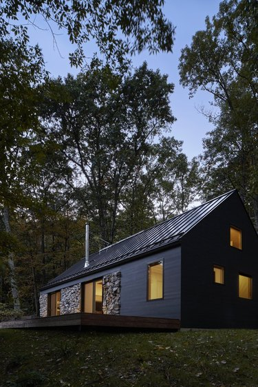modern barn-like cabin with black metal roof and matte black siding