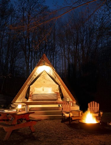 nighttime glamp setup with bonfire and wooden lounge chairs