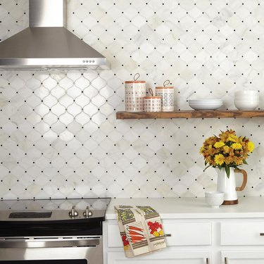 white kitchen with arabesque tile backsplash featuring black dots