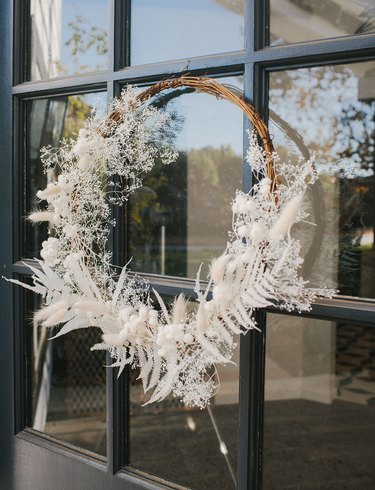 Christmas Door Decorations with Twig wreath with white dried flowers, feathers.