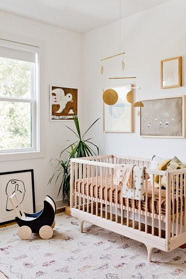 white minimalist nursery decor with wood crib and rug