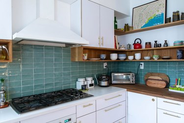 kitchen with blue tile backsplash, white cabitnets, white range hood and stove top