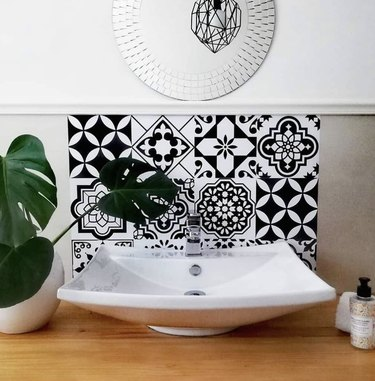 small bathroom backsplash ideas with black and white wall tiles and circle mirror