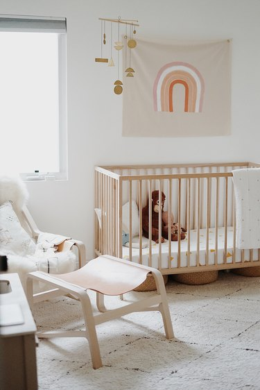 white minimalist nursery decor with crib and hanging art
