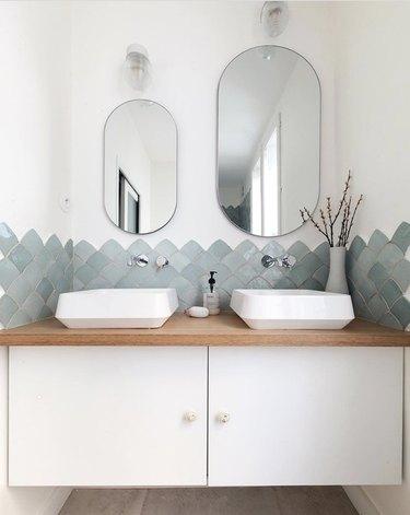 small bathroom backsplash ideas in modern bathroom with grey-green zellige tile and oval mirrors