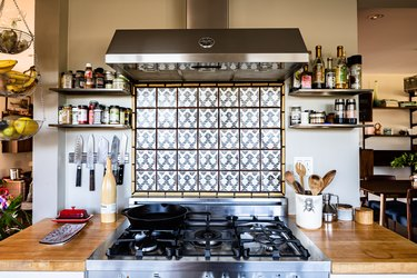 stainless steel range hood, accent tile backsplash and stove