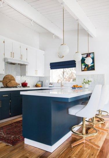 blue and white u-shaped kitchen with globe style pendants