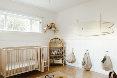 white minimalist nursery decor with wood crib and surf board on the wall