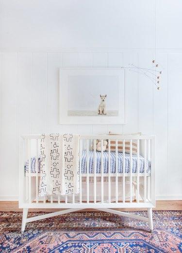 white minimalist nursery decor with colorful vintage rug and white crib