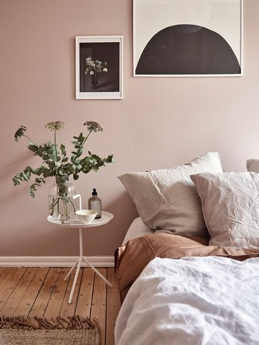 pink and taupe minimalist bedroom idea with wooden floors