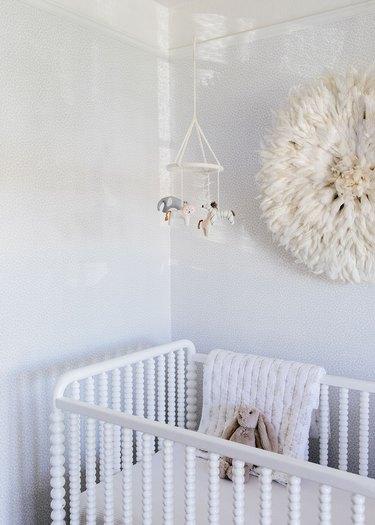 white minimalist nursery decor with white crib and wall art