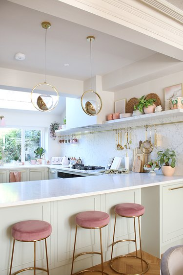 white kitchen with pink stools and open shelves