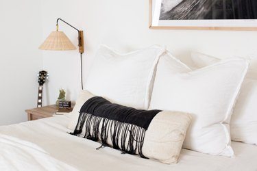 bed with fringe pillow and white pillow with lamp nearby