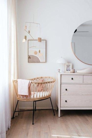 white minimalist nursery decor with bassinet in the corner