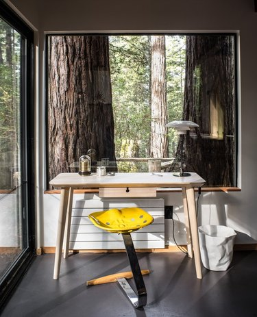 modern desk home office space in forest setting with picture window