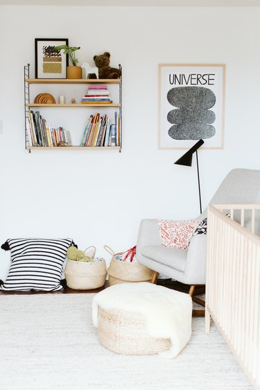 white minimalist nursery decor with wall-mounted shelving and floor poufs