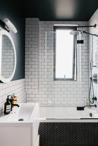 bathroom shower with white subway tile, window and white sink