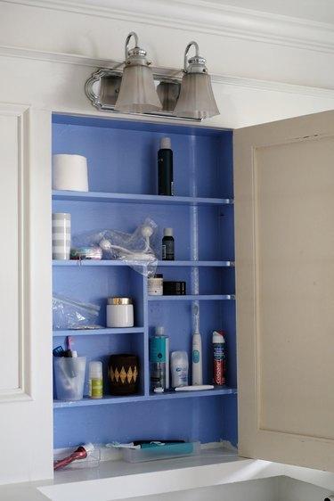 blue medicine cabinet interior featuring personal hygiene supplies